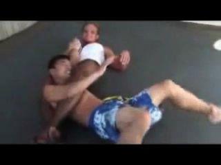 혼합 레슬링 담황색 여자가 약한 사람을 잠근다.