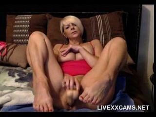 더 나이 들었던 금발의 유부녀가 침대에서 그녀의 음부와 함께 노는