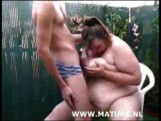 뚱뚱한 암캐 정원에서 수탉을 빠는 그녀의 가슴 크림을 받고