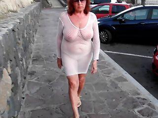 아름다운 성숙한 매춘부는 알몸의 가슴으로 도시를 산책합니다.