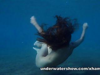 줄리아는 바다에서 수중 누드를 수영하고있다.