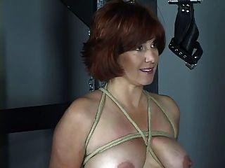 멋진 가슴과 엉덩이를 가진 누드 빨간 머리가 bdsm 던전에서 휘저어진다.
