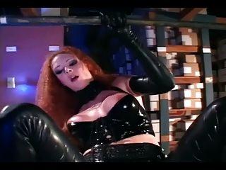 섹시한 빨간 머리가 반짝이는 검은 색 라텍스에 빠져 들었다.