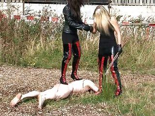 두 명의 엄격한 승마 여주인이 노예를 태우고 채찍질한다.