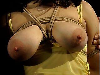 노란 드레스 바운드에 큰 가슴의 매력과 그녀의 가슴에 옷 못으로 덮여있다.