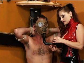 빨간 드레스에 섹시한 지배자가 지하 감옥에서 담배를 피우며 노예를 태운다.