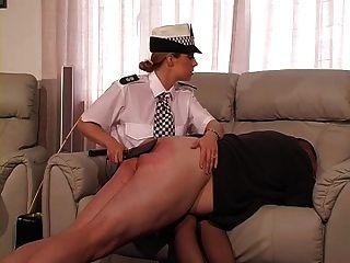 여성 영국 경찰은 벌을 받고 지팡이를 쓴다.