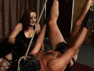 빨간 머리 dominatrix는 남자 엉덩이를 때려 눕힌다.