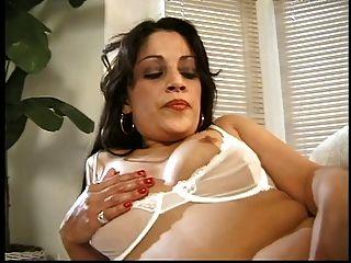 어두운 머리의 베이비는 소파에 낳고 그녀의 면도 한 상자 안에 손가락을 밀어 넣습니다.