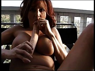 busty redhead는 높은 목제 발코니에 양면 향이 나는 딜도 라구 딜도와 함께 그녀의 여자를 성교시킵니다.
