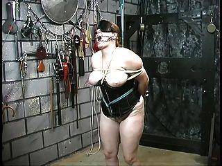 코르셋에서 귀여운 두꺼운 노예 소녀는 그녀의 주인에 의해 제지되고 굴욕 당한다.