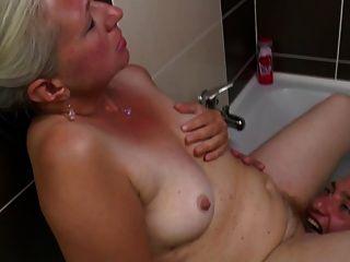 오래된 엄마가 화장실에서 젊은 수탉을 데려 간다.