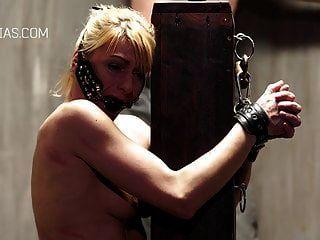 가난한 노예 소녀가 기둥에 묶여 가혹하게 휘저었다.
