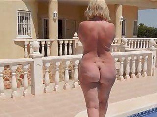 벌거 벗은 둥근 엉덩이를 가진 성숙한 여인이 수영장 옆으로 걷는다.